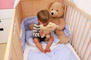 Ein zweijähriger Junge sitzt weinend in seinem Kinderbett