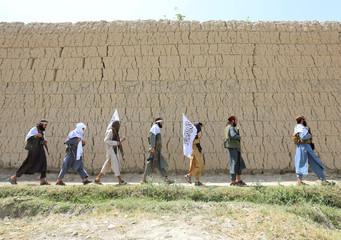 Taliban walk as they celebrate ceasefire in Ghanikhel district of Nangarhar province, Afghanistan