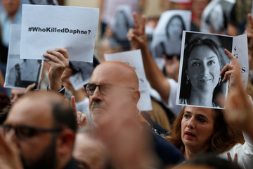 People attend a vigil and demonstration marking eight months since the assassination of investigative journalist Daphne Caruana Galizia in a car bomb, in Valletta