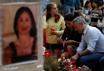 Former Opposition leader Simon Busuttil and his partner Kristina Chetcuti light candles during a vigil and demonstration marking eight months since the assassination of investigative journalist Daphne Caruana Galizia in a car bomb, in Valletta