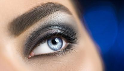 Woman blue eye with perfect makeup. Beautiful professional smokey eyes holiday make-up. Eyebrows shaping, eyes and eyelashes. Skin care