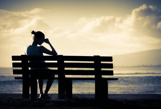 Sad woman sitting on park bench.