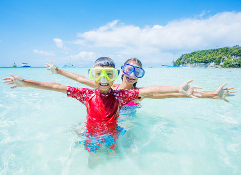 Two happy kids in diving masks having fun on the beach