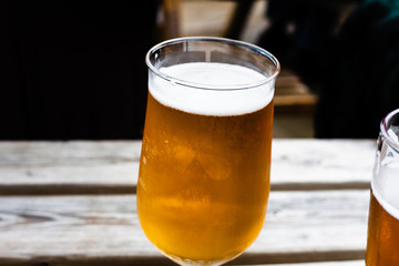 Glass of beer on the wooden table. Draft beer served at the bar. Glass of light beer on the wooden board. Served alcoholic drinks in a glass. Alcoholic beverage with blurred background.