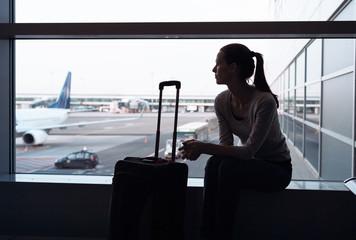 Female traveler waiting for her flight at airport.