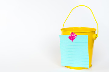 Illustration of bucket list concept with yellow metal bucket and list taped to front against white background
