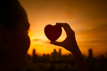 Young female holding up heart in the sky against a city sunset. Love happiness concept.