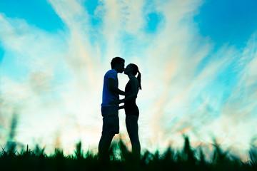 Man and woman kissing at sunset.