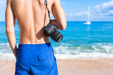 Male traveler on the beach holding camera.