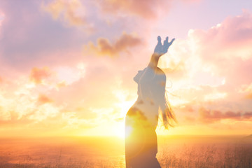 Happiness and joy.  Young female feeling free in the sunset with arms up in air. Double exposure