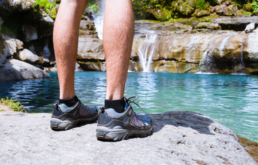 Hiking and adventure concept. Male hiker's feet standing next to mountain spring.