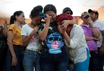 Family members and friends mourn the victims of a fire that broke out in a building in Managua