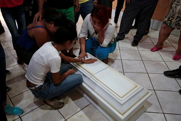 Family members and friends mourn as they touch a coffin containing the body of a child who died after a building caught fire, in Managua