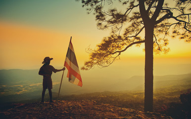 Silhouette Scouts with the Thai flag stand on a cliff at sunrise.
