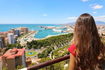 Back view of young woman looking to Malaga cityscape in her travel in Spain