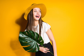 laughing long-haired girl model in a fashionable hat holds a green leaf and posing on an orange background