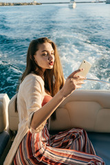 beautiful long-haired girl in stylish summer clothes rests on a yacht, makes selfie on her smartphone in the sun
