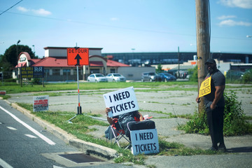 Scalpers advertise the need of tickets near the entrance on the third day of the Firefly Music Festival in Dover, Delaware U.S.