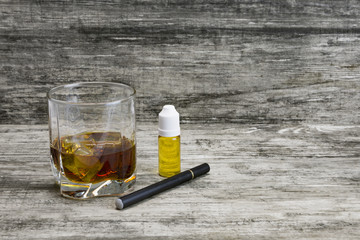 Whiskey in a glass with an e-cigarette and liquid for it on a gray stone background
