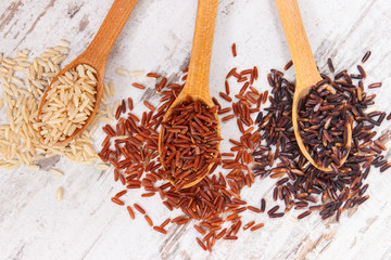 Brown, red and black rice on wooden spoon, healthy nutrition concept