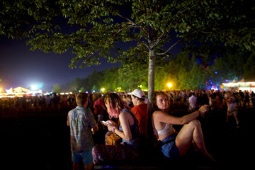 Grace Kennedy, 19, rests against a tree while others use their smartphones on the third day of the Firefly Music Festival in Dover, Delaware U.S.