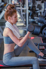 Attractive young sports woman lifting weights in the sport gym ,bodybuilding and loose weight concept.