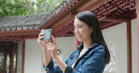 Woman taking photo on cellphone in Chinese garden