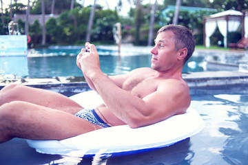 Young man relaxing on the pool, using mobile phone. Work and relaxation