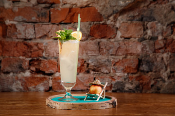 Refreshing cocktail with alcohol, mint, orange and ice in tall glass. Peach is lying on chaise longue on beach.