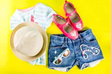 Summer vacation concept, summer child's cloth set - kids shorts, T-shirt, hat, sun glasses, bracelet necklace, sneakers, bright yellow background above flat lay copy space