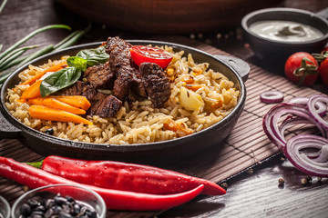 The concept of eastern, Uzbek cuisine. Pilaf, plov in a black cast-iron frying pan on a wooden table, next to lie ingredients, onions, tomatoes, parsley, pepper. Central Asian cuisine.