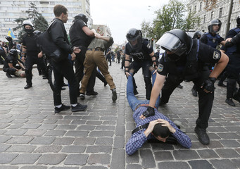 Riot police officers detain anti-LGBT protesters during the Equality March in Kiev