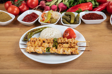 Grilled chicken on bamboo skewers. Chicken kebab on plate, close up view.