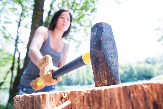 Asian woman chopping wood