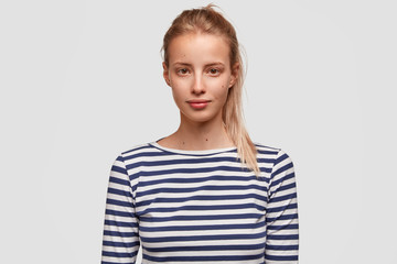 Horizontal shot of pretty female with light hair combed in pony tail, wears sailor sweater, listens attentively interlocutor, poses against white background. Confident woman looks directly at camera