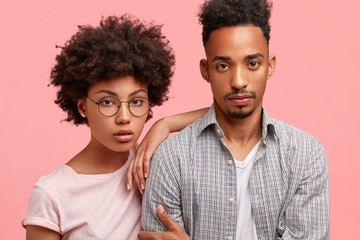 Lovely African American couple stand close to each other, look seriously at camera, have confident expressions, dressed in casual outfit, pose together against pink background. Companionship concept