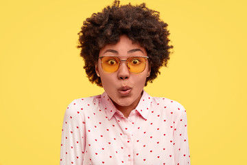 Close up portrait of puzzled young African American female looks in bewilderment, expresses great suprisement, being impressed by something unbelievable, wears blouse, stands against yellow background