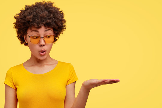 Horizontal shot of amazed fashionable female youngster with dark skin and Afro hairstyle, keeps palm raised as if holds something, advertises blank space wears casual yellow t shirt, bright background