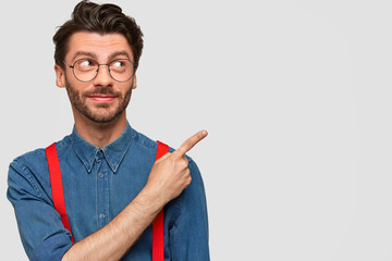 Fashionable unshaven guy with pleased expression, wears stylish clothes, indicates with fore finger aside at copy space, stands against white background. People, lifestyle and advertisement concept
