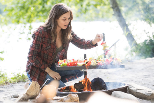 Woman cooking vegetable skewers over camp fire