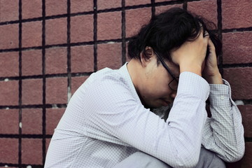 Close up frustrated stressed Asian business man in depression with hands on forehead
