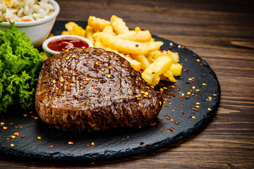 Deurstickers Steakhouse Grilled steak with french fries and vegetables served on black stone on wooden table