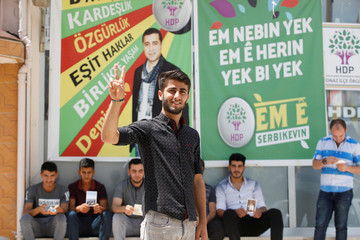 Birhat Demir, a candidate for the pro-Kurdish HDP in the June 24 parliamentary election, flashes a V-sign during an election campaign in Denizli