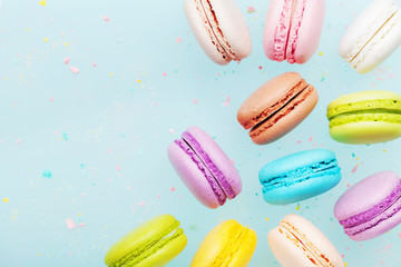 Foto auf Leinwand Macarons Flying cake macaron or macaroon on blue pastel background. Colorful almond cookies on dessert.
