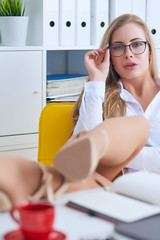 Office flirt - attractive woman flirting over desk with her coworker or boss.