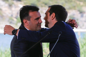 Greek Prime Minister Alexis Tsipras and Macedonian Prime Minister Zoran Zaev hug before the signing of an accord to settle a long dispute over the former Yugoslav republic's name in the village of Psarades