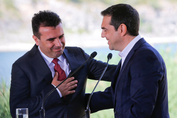Greek Prime Minister Alexis Tsipras and Macedonian Prime Minister Zoran Zaev gesture before the signing of an accord to settle a long dispute over the former Yugoslav republic's name in the village of Psarades