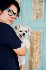 Asian woman hugging dog so cute with wooden wall