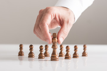 Man playing a game of chess on white table in a close up view