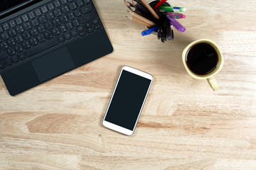 blank screen smartphones and labtop on the wooden desktop and a cup of coffee in composition with copy space for your text